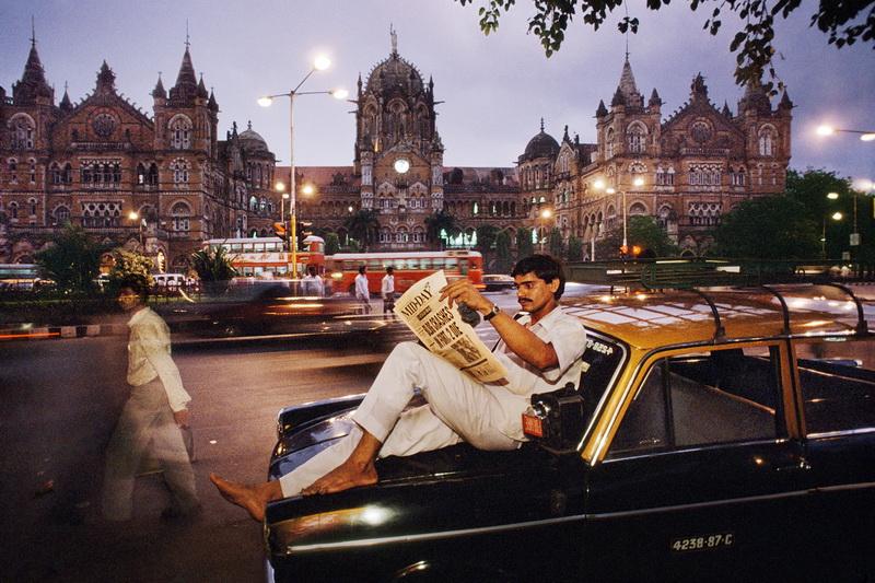 Man Reading a Newspaper on a Taxi. Mumbai, India, 1996 © Steve McCurry